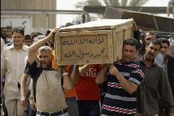 Relatives carry the coffin of a policeman killed Sunday by a suicide bomber outside the police academy in Baghdad.