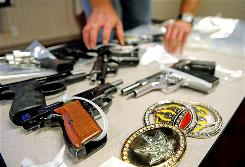 A DEA field agent packs up weapons that were confiscated during a raid in Gwinnett County, Ga., in September.