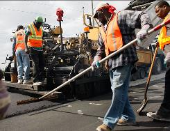 A road construction crew works on a widening project in February in Florida City, Fla. The stimulus law calls for infrastructure projects to help spark the economy.