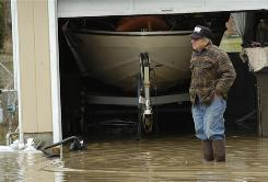 John Robinson stands in front of his garage Monday after checking on his sump pump in Findlay, Ohio
