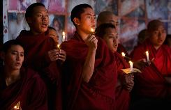 Tibetan monks in exile look on during a candle lit vigil to commemorate 50 years in exile on March 10 in Dharmsala, India.