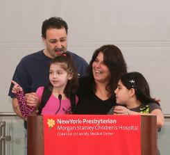 Heather McNamara, in front of microphone, with her sister Stephanie and parents Joseph and Tina before her release Tuesday from New York-Presbyterian Morgan Stanley Children's Hospital.
