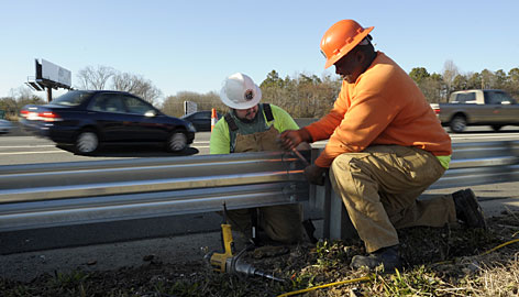 Department of Transportation workers Cory Cravens, left, and Willie Lockamy install guardrails along I-85/40 in North Carolina.