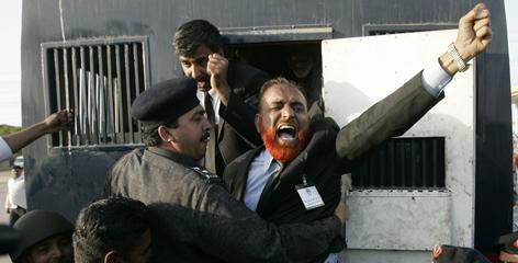Police officers arrest a protester taking part in an anti-government march Thursdaty in Karachi, Pakistan.