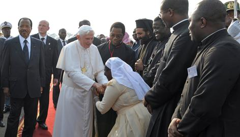 Pope Benedict XVI, flanked by Cameroonian President Paul Biya, left, is greeted by a Cameroonian nun on arrival at the airport in Yaounde on Tuesday.