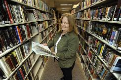 Librarian Karen Hayden looks over 'Tidwick The Big Hearted Moose' by Dr. Seuss as she stands in the stacks of the Little Dixie Regional Library in Moberly, Mo. Federal regulators say that librarians should limit access to books that were printed before 1985 because the ink may contain lead.