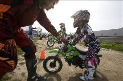 Bonnie Warch helps Karsyn Boyd, 6, with her dirt bike Feb. 15 at the School of Dirt in Irvine, Calif.