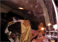 Media and curious onlookers swarm the SUV carrying Nadya Suleman, the mother who gave birth to octuplets, as she returns to her home in La Habra, Calif., with two of the babies late Tuesday night.