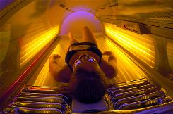 A college student rests in a tanning bed in preparation for spring break.