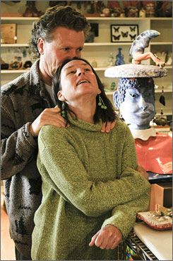 Alex and Antonia Lawson cuddle in her ceramic studio at their home in San Rafael, Calif.