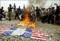 Iraqi Shiites burn a U.S. flag on Friday in Baghdad's Sadr City.