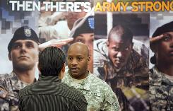 Army recruiter Staff Sgt. Roderick Brown talks to an unidentified person at a job fair in Omaha on Tuesday. The jobless rate for veterans who served in Iraq and Afghanistan and who are 18 and older rose 4% in the past year.
