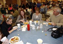 From left, Niki Plowright joins Lisa Mann and her mother, Shelly Mann, and Sherwood Owens during the Lenten Friday fish fry at St. Frances Cabrini Catholic Church in Littleton, Colo., on March 13.