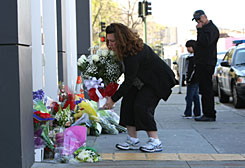 A woman leaves a bouquet of flowers in front of the Oakland police department in a memorial to four Oakland police officers that died in the line of duty Sunday.