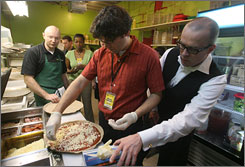 Depaul student Lucas Weingarten, second from right, and assistant professor Patrick Murphy, right, lend a hand Tuesday.
