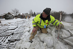 Rick Larson, an engineering technician for Fargo, N.D., measures the height of the sandbag dike near homes along the Red River on Wednesday.