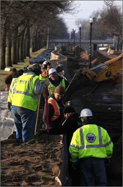 Subcontractors for Wanzek Industrial contractors work to protect a neighborhood along the Red River in Fargo on Tuesday.