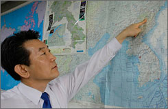 The Rev. Chun Ki Won of the Durihana Mission, an organization that helps defectors from North Korea, points to a border village on a map during an interview from his office in Seoul on Wednesday. The minister says he repeatedly warned American journalists not to sneak over the border into North Korea.