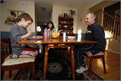 Matty Billemeyer, left, talks with his mother Deanne and father Darryl while eating dinner at their home in Doylestown, Pa. Matty is just 8 years old but already has had four bouts with kidney stones; he was first stricken in his first-grade class.