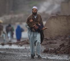 A Pakistani man carries his son after a storm at the Jalozai refugee camp near Peshawar, Pakistan, in February. U.S. efforts to provide aid and dry up terrorist support in impoverished areas there have barely begun because of fears of corruption and bureaucracy.