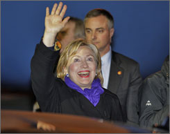 Secretary of State Hillary Rodham Clinton waves as she arrives at Schiphol airport.