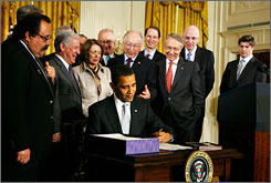 President Obama signs the Christopher and Dana Reeve Paralysis Act on Monday, with Reeve's son Matthew, far right, looking on.
