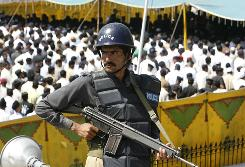 A policeman stands guard during a funeral for those killed in an attack at a police training center Tuesday in Lahore. Pakistani Taliban leader Baitullah Mehsud took responsibility for the deadly assault.