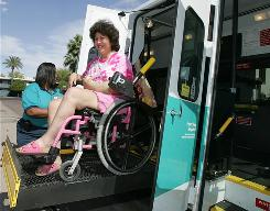 Brenda Vance, left, helps Desirrie Ramirez into a paratransit van at Central Phoenix Adult Day Care. It's hard for many cities to maintain the services.