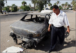 An Iraqi policeman is seen on Sept. 20, 2007, inspecting a car that had been destroyed by Blackwater security detail in Baghdad four days earlier.