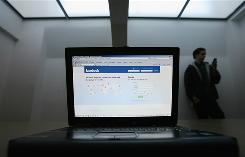 A guy checks his cellphone for messages as a laptop screen displays the Facebook homepage. The mobility of electronics has had a profound effect on kids' lives, even in the past five to ten years, researchers have found.