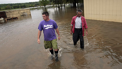 Matt Galloway, left, and Vance Langham walk Wednesday through receding floodwaters that inundated the River Oaks Golf Course in Geneva, Ala.
