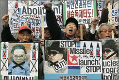 Protesters holding portraits of North Korean leader Kim Jong Il shout slogans Monday during a rally in Seoul denouncing the North's missile activity.