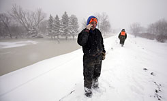 Fargo resident Scott Manthe talks on the phone as he stands on the snow-covered earthen levee in blizzard conditions in Fargo, N.D., on Tuesday. Red River floodwaters continue to drop along 76th Ave. South. In the background. members of the South Dakota National Guard patrol the levee.