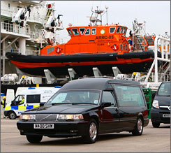 A hearse carrying bodies from a helicopter crash off Scotland's coast in the North Sea drives away from a support ship, the Caledonian Victory, in Aberdeen harbor, Scotland, on Thursday.