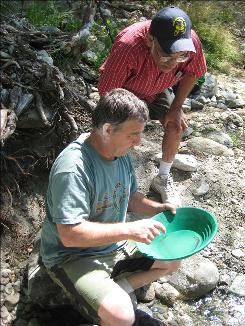 Mike Gavin, front, pans for gold with Mike DeMello along the San Gabriel River in Los Angeles County.