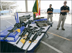 Customs and Border Protection officers stand by guns confiscated along the U.S.-Mexico border.