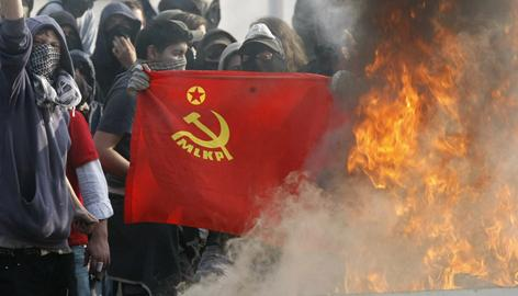 Hooded anti-Nato demonstrators hold a flag near a burning barricade in a stand off against French riot police forces Friday in the southern suburbs of Strasburg.