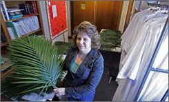 """Laura Hudson shows palm fronds at Holy Trinity Lutheran Church in Columbus, Ohio. """"We believe that God created the Earth, and it's our job to preserve it the best we can,"""" she says."""