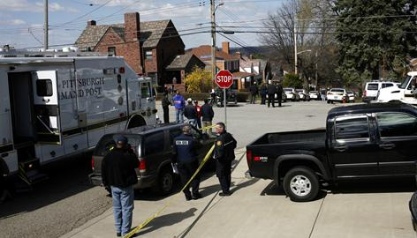 Pittsburgh police officers and onlookers stand near the scene of a police shooting Saturday.