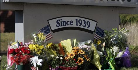 Flowers lay at the base of a sign in front of the American Civic Association on Sunday in Binghamton.