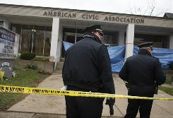 Police officers stand in front of the American Civic Association on Saturday where a gunman killed 13 people in Binghamton, N.Y.
