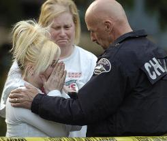"A Pierce County deputy comforts a relative of the slain children on Saturday in Graham, Wash. ""This was not a tragedy. It was a rotten murder,"" Pierce County Sheriff Paul Pastor said."