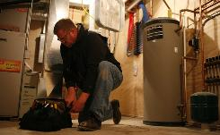 Tim Detrick, 42, works to un-install a temporary furnace at a new home outside Mason City, IA. Detrick went back to school after being laid off from his job at IMI Cornelius a company building and suppling beverage dispensers.
