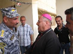 Bishop Shlemon Warduni of the Chaldean Catholic Church meets with Iraqi police Col. Samir al-Timimi in Dora. Al-Timimi has been working with Warduni to try to persuade Christian families, who fled in the midst of sectarian violence, to return to Dora.