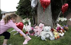 A girl places a stuffed animal at a memorial for Sandra Cantu in Tracy, Calif., on Thursday. The body of Cantu, 8, was discovered inside a suitcase in an irrigation pond.