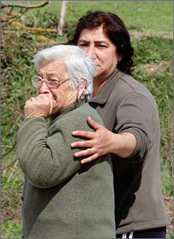 Two women cry Thursday as they walk through a tent camp in Onna, Italy, set up to house survivors of an earthquake that struck Monday.