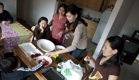 Once a refugee herself, Regina Lee, top center, mentors a group of Bhutanese refugee women in Maryland, bringing Jell-O to their home and helping them adjust to life in the U.S.