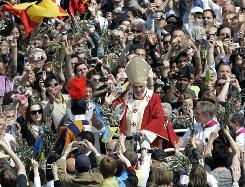 Pope Benedict XVI blesses faithful after celebrating an open-air Mass on Palm Sunday in St. Peter's Square. As many as 100,000 people are expected to attend Easter Mass there on Sunday.