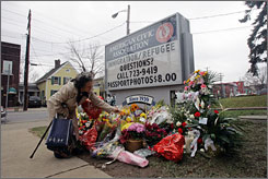 Louise Backus of Binghamton, N.Y., adds flowers to a memorial pile in front of the American Civic Association offices in the same city on Tuesday. Last Friday, the building was the scene of a mass shooting that ended with 14 people dead.