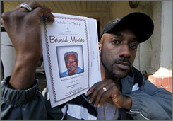 Shaun Monroe holds up a program from the funeral of his father, Bernard Monroe, on March 18 at his father's home in Homer, La.